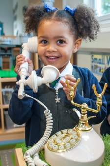 A pupil using a play telephone at Willow Tree Primary School